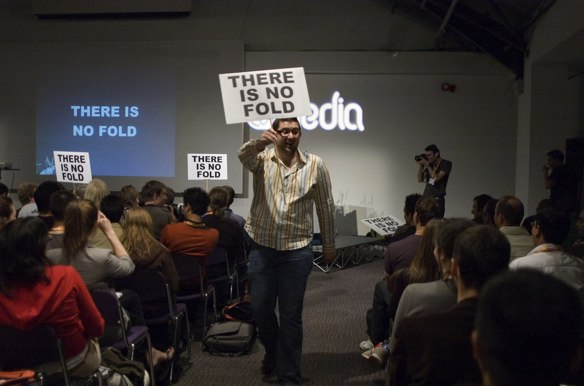 A web deisgner holding a 'there is no fold' banner