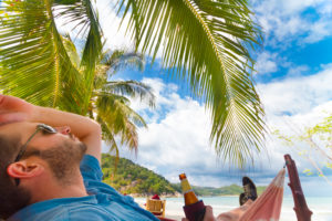 Man relaxing on a tropical beach with a bottle of beer in his hand.